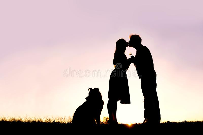 Silhouette of Loving Young Couple Kissing Outside on Date at Sun stock photo