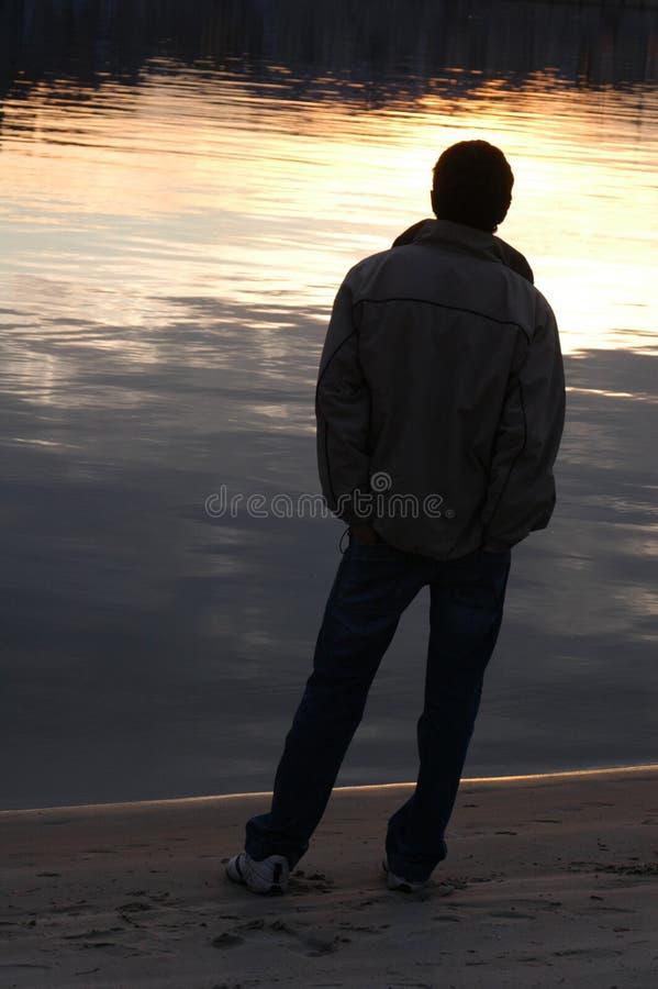 Silhouette mâle au coucher du soleil image stock