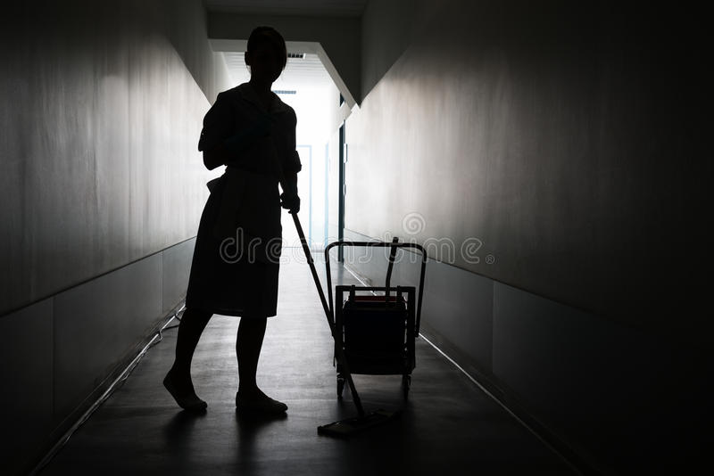 Silhouette of maid cleaning floor royalty free stock images