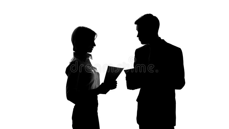 Silhouette of male boss jawing his secretary because of mistakes in report stock photos