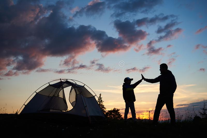 Silhouette of male and child give each other high five near tent at dawn. Silhouette of men and child hikers give each other a high five near the tent at dawn stock photography