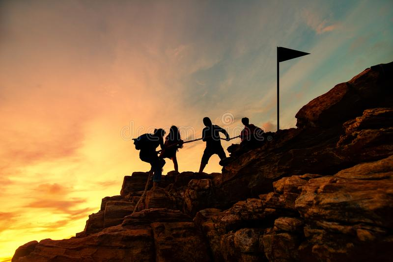 Silhouette male and female hikers climbing up mountain cliff, Helps and team work concept. stock image
