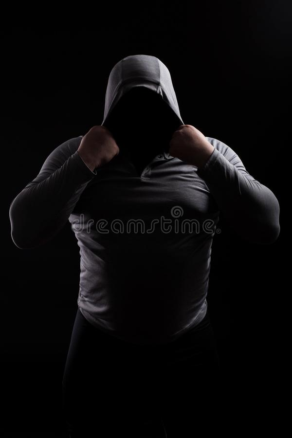 Silhouette of a male fight club in a hood without a face. Stalker silhouette on black background, incognito, anonymous, dangerous. Man, thug in the dark. Sporty royalty free stock photo