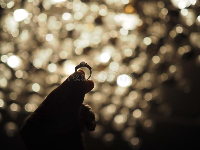 Silhouette of a male hand holding a large diamond ring with yellow bokeh light background. Selected focus stock photography