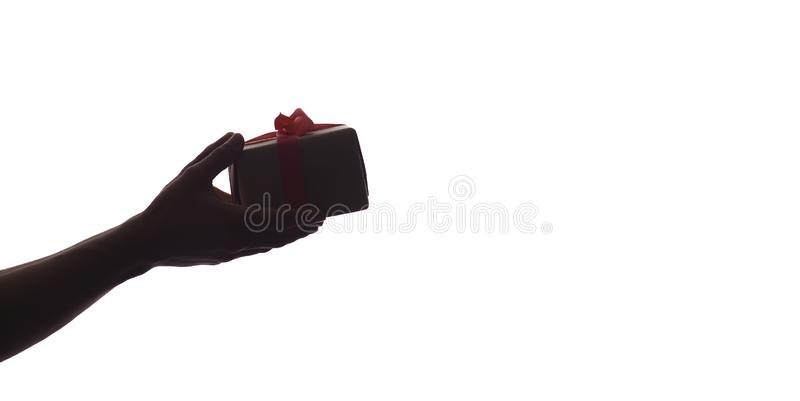 Silhouette of male hands giving a gift box with bow for his beloved on white isolated background, concept holidays, care, surprise royalty free stock photography