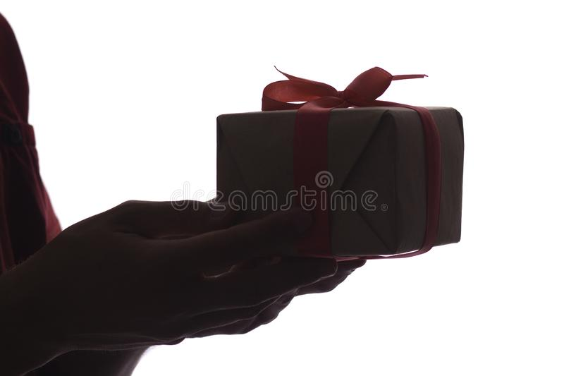 Silhouette of male hands giving a gift box with bow for his beloved on white isolated background, concept holidays, care, surprise royalty free stock images