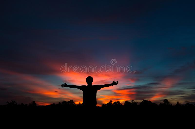 Silhouette of a male holding hands at sunrise stock images