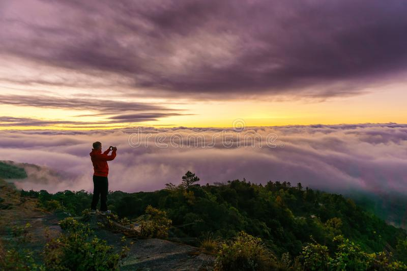 Silhouette of male photographer or traveler taking a photograph sunrise landscape on mountain top at Doi Inthanon National Park royalty free stock image