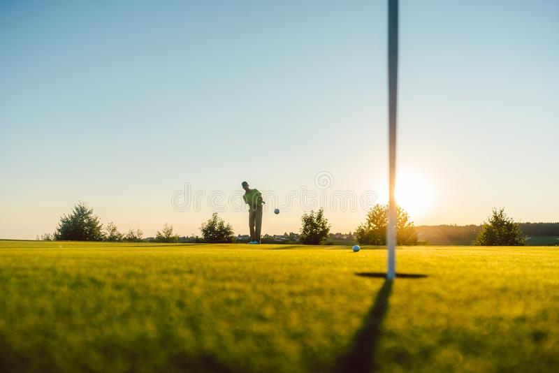 Silhouette of a male player hitting a long shot on the putting g. Full length view of the silhouette of a male player hitting a long shot on the putting green stock image