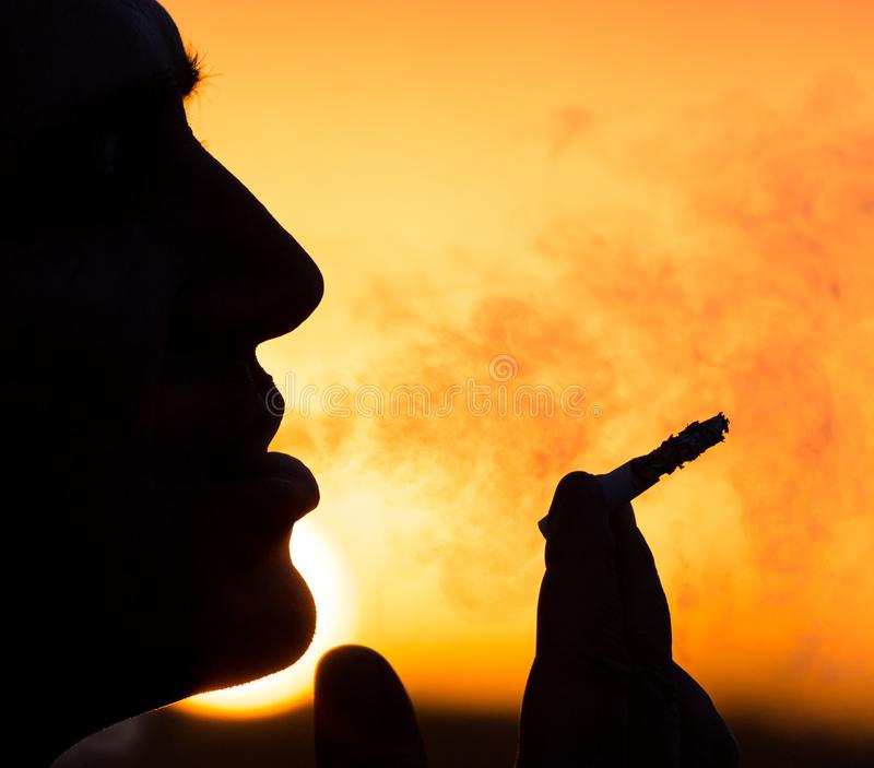 Silhouette of male smokers in the sunset stock photography