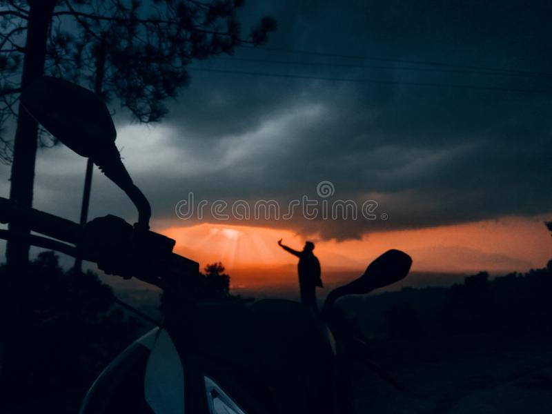 Silhouette of a male taking a picture with a beautiful sky in the background stock photo