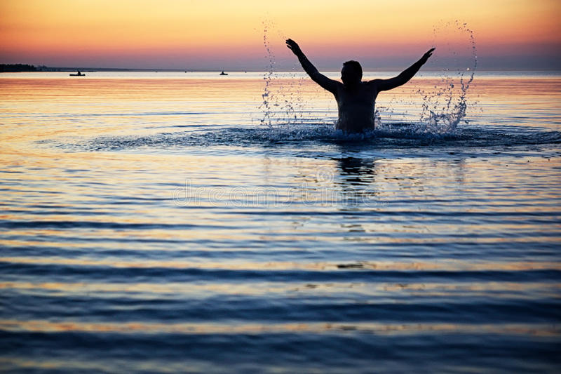 Silhouette of a male in the water stock images