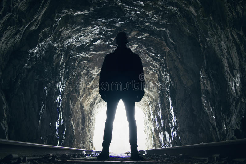Silhouette of man in abandoned railway tunnel. Silhouette of a man standing in front of the opening in an abandoned cave like railway tunnel stock photos