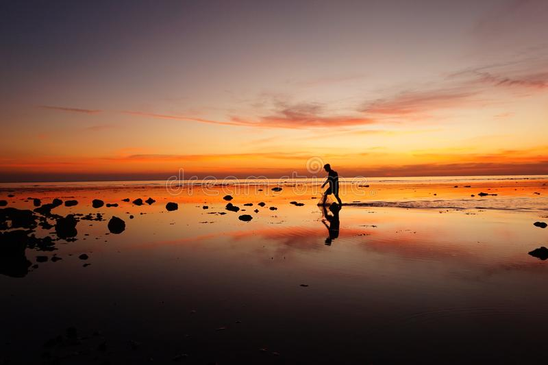 Silhouette Man Across Sunset Moment. Captured at one of the beautiful beach in Bawean island, East Java, Indonesia royalty free stock photos