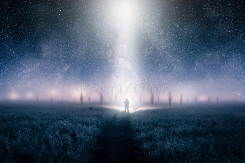 A silhouette of a man as ghostly alien figures appear through the mist with lights appearing in the sky with a light beam coming d stock photos