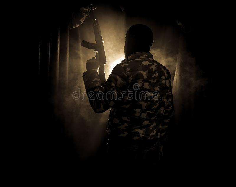 Silhouette of man with assault rifle ready to attack on dark toned foggy background or dangerous bandit in black wearing balaclava stock photography