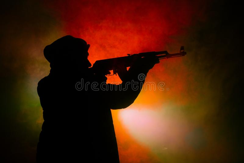 Silhouette of man with assault rifle ready to attack on dark toned foggy background or dangerous bandit in black wearing balaclava royalty free stock photos