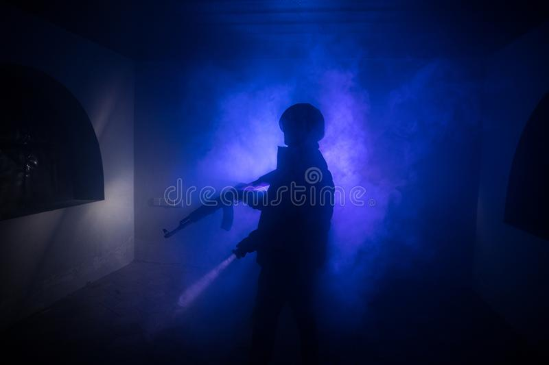 Silhouette of man with assault rifle ready to attack on dark toned foggy background or dangerous bandit in black wearing balaclava stock photo