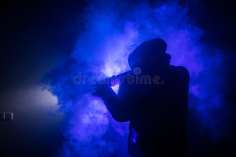 Silhouette of man with assault rifle ready to attack on dark toned foggy background or dangerous bandit in black wearing balaclava stock photos