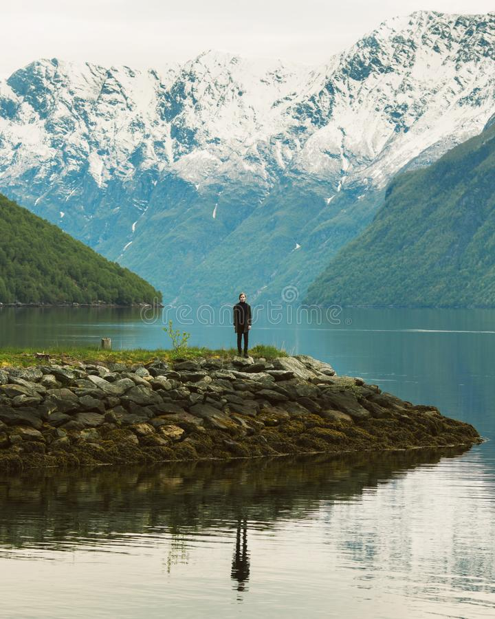 Silhouette of a man on background of mountains in Norway. Beautiful landscape with fjords in Norway. Tourist stands against the stock image