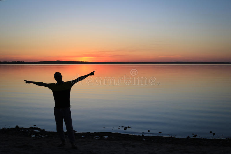 Silhouette of Man at the beach in the Sunset stock photo