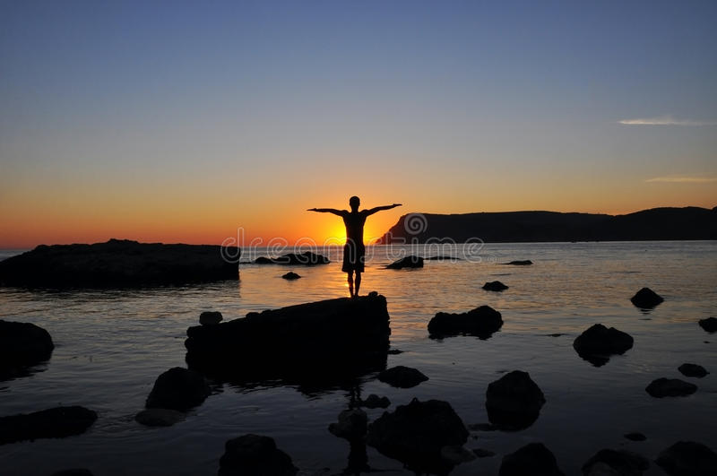 Silhouette of a man on the beach at sunset preparing to jump off. A cliff into the water stock images