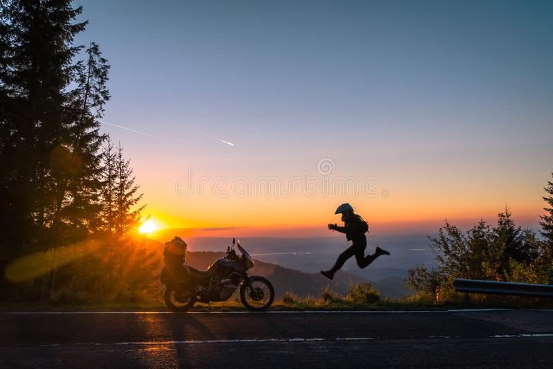Silhouette of man biker and adventure motorcycle on the road with sunset light background. leap with joy. Top of mountains, royalty free stock images
