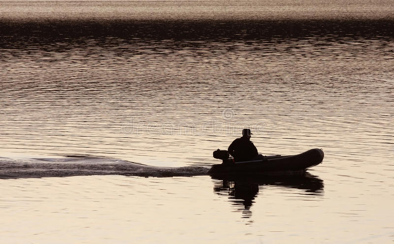 Silhouette of a man in a boat. On the water, the trace of the boat royalty free stock images
