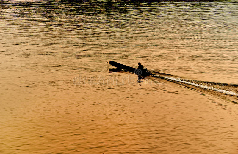 Silhouette of a man in a boat. At sunset in Sangkhlaburi ,Thailand royalty free stock photo