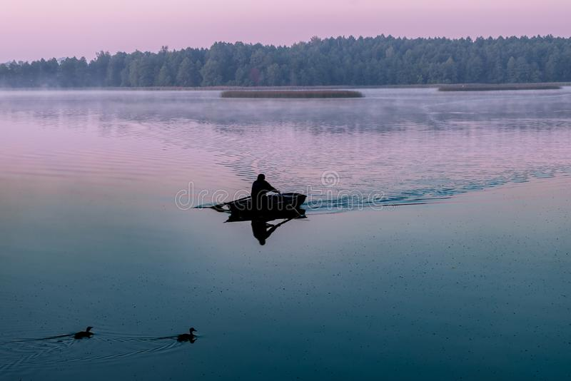 Silhouette of man in a boat in the early morning. pink dawn with ducks royalty free stock photography