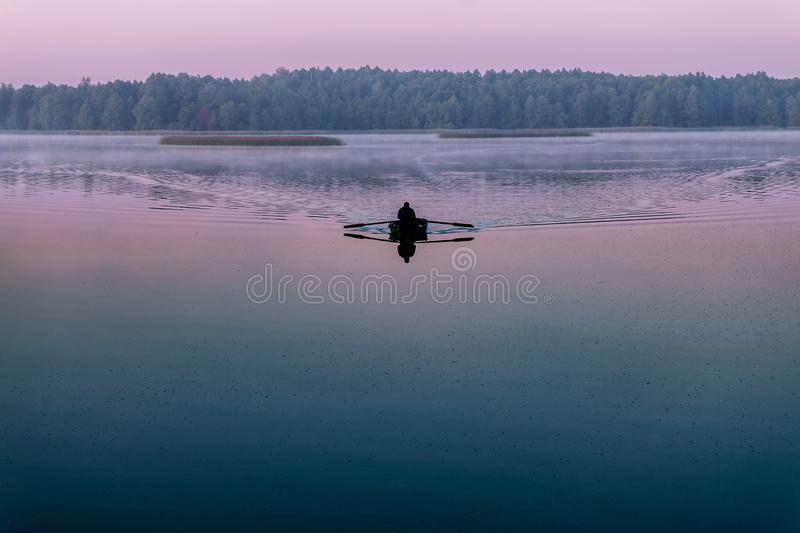 Silhouette of man in a boat in the early morning. pink dawn stock image