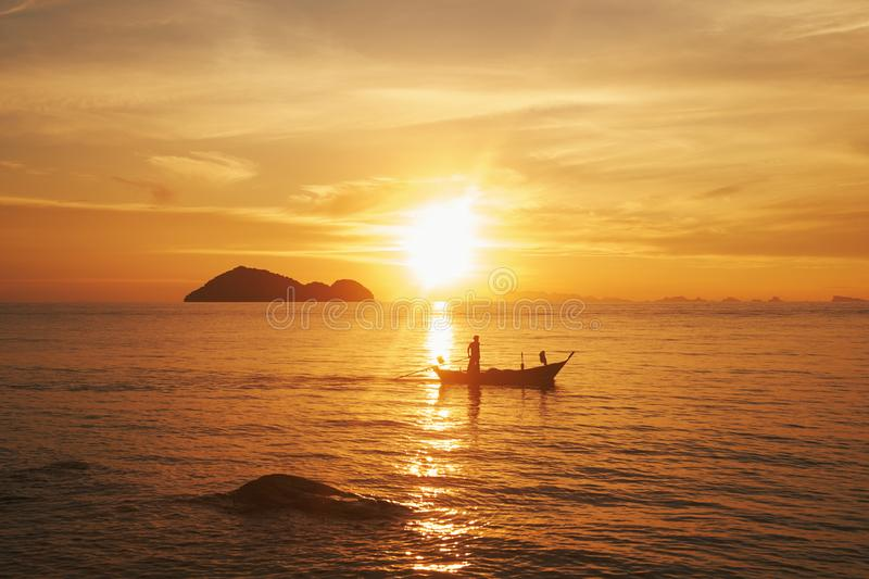 Silhouette of man in the boat in a sea. Sunset. Thailand, Phangan. Silhouette of man in the boat in a sea. Ocean sunset. Thailand, Phangan - image royalty free stock image