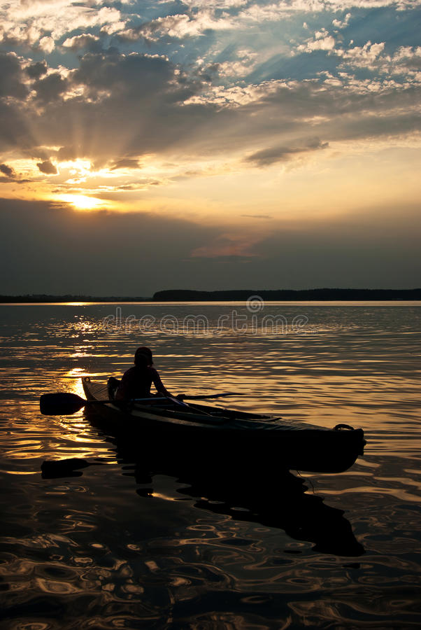 Silhouette of a man in a boat. At sunset, backlight stock images