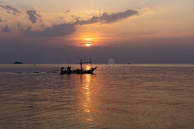Silhouette of a man on a boat during sunset at sea. Water. Thailand stock photos