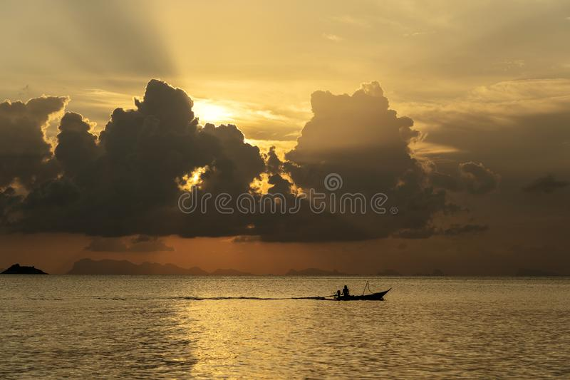 Silhouette of a man on a boat during sunset at sea. Water. Thailand stock photo