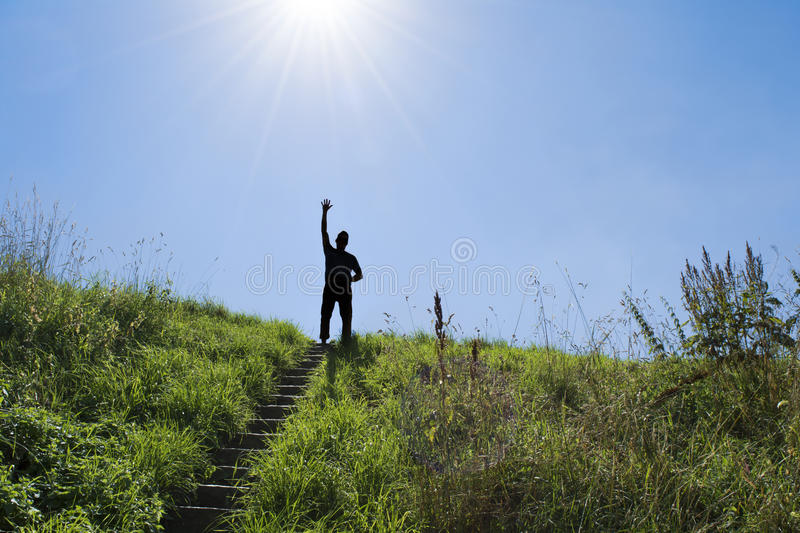 Silhouette of man in bright sunlight on top of a stairs. Silhouette of man in bright sunlight on top of an outdoor stair. Waving triumphantly royalty free stock photography