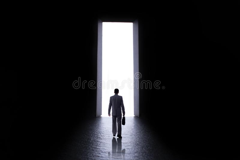 Silhouette of a man in a business suit with a briefcase in making step to open door into the unknown, the concept of life choices. Silhouette of a young man in a royalty free stock photo