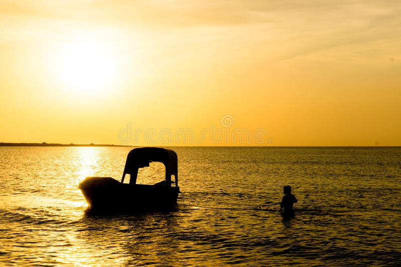 Silhouette of man carrying the anchor of boat out to sea. Silhouette of man carrying the anchor of his boat out into the sea to the floating boat. Shot at royalty free stock images