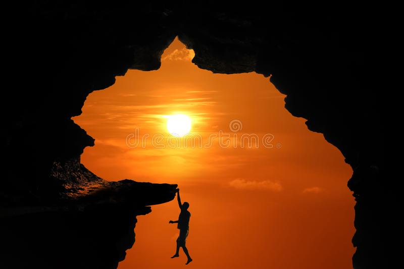 Silhouette of Man climbing in the cave or high cliffs at a red sky sunset stock image