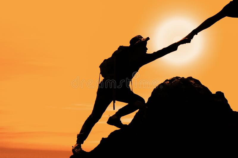 Silhouette of man climbing up mountain with hand giving help royalty free stock photography