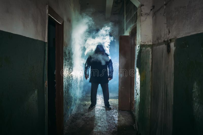 Silhouette of man in cloud of smoke standing in dark scary corridor stock photography