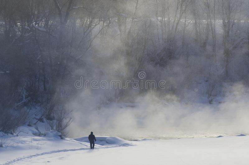 Silhouette of a man on the coast of the frozen river with fog stock image