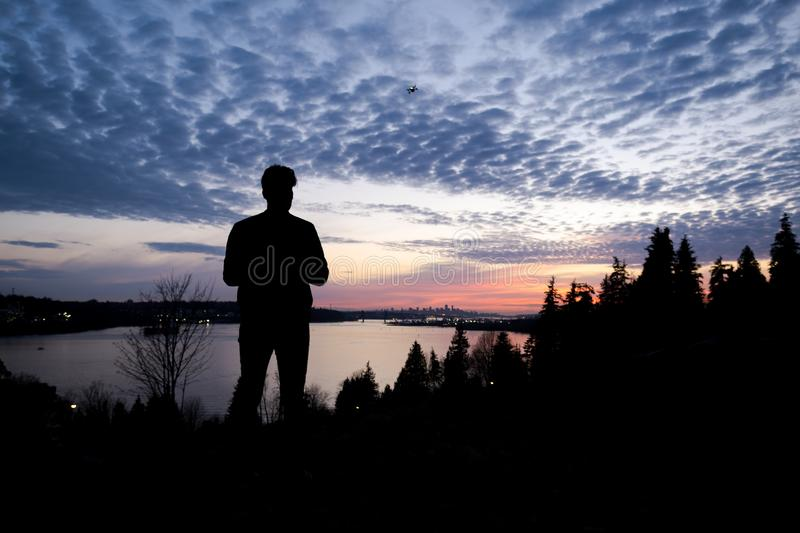 Silhouette of a man controlling a drone that is in the background with the sun setting over downtown Vancouver. royalty free stock images