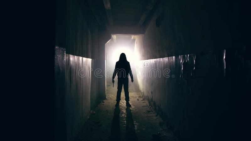 Silhouette of man in dark creepy and spooky corridor stock photo