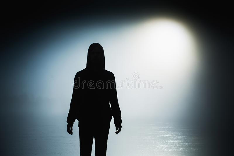 Silhouette of a man in the darkness. Night photography. Shadow in mist. Mysterious anonymous figure in darkness. Incognito person royalty free stock photo
