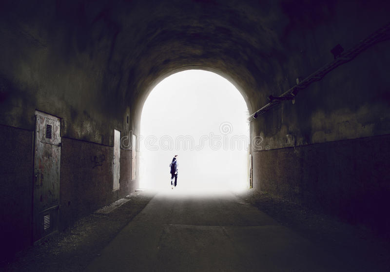 Silhouette of a man disappearing into the light at the end of a tunnel. Vanishing silhouette of a man disappearing into the light at the end of a tunnel. Rough royalty free stock images