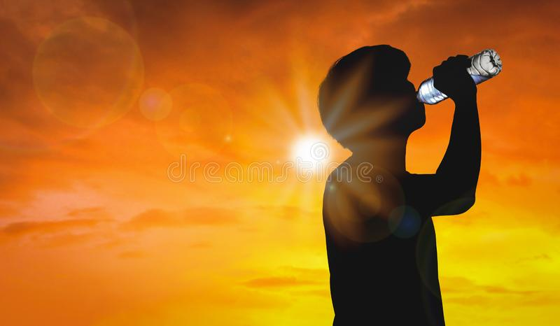 Silhouette man is drinking water bottle on hot weather background with summer season. High temperature and heat wave concept royalty free stock photography