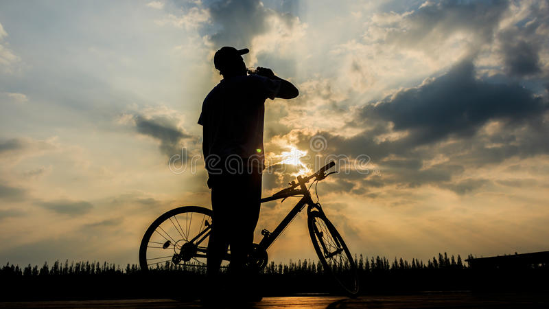 silhouette of man drinking water at lake sunset time after intense cycling training, royalty free stock photos