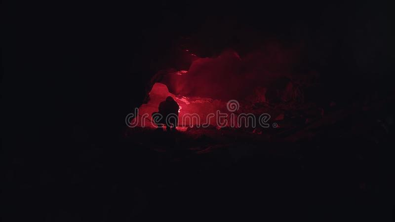 Silhouette of a man exploring a cave with a red burning signal flare in complete dark. Stock footage. Male royalty free stock photos