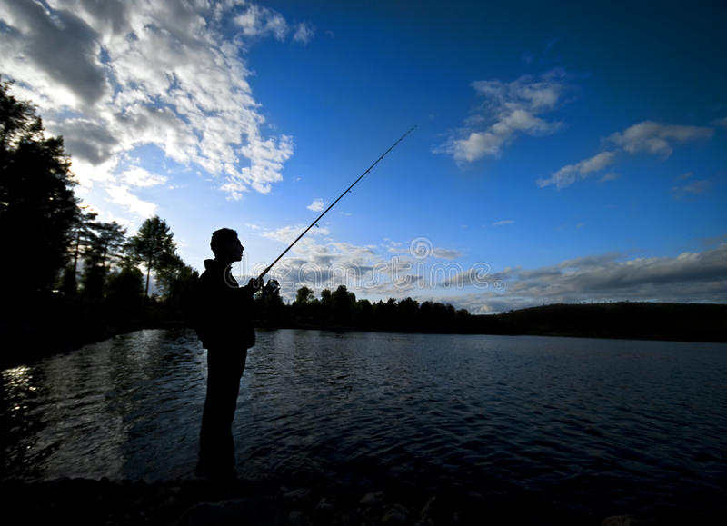 Silhouette Of Man Fishing Stock Photo